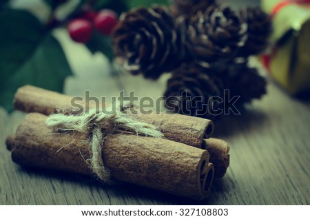 Cinnamon sticks, tied in a bundle with string on an oak table with Christmas holly, fir cones and a gold wrapped gift box in the background. Cross processed for retro or vintage effect. - stock photo