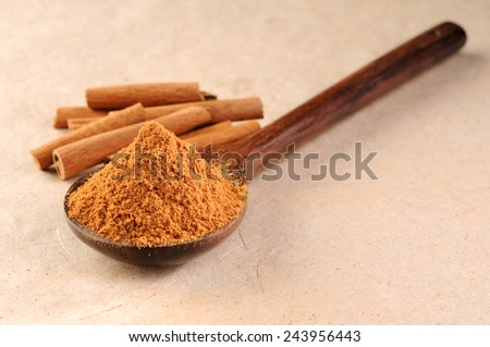 cinnamon sticks with cinnamon powder in a wooden spoon - stock photo