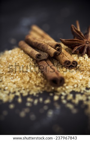 Cinnamon, sugar and star anise on black - stock photo