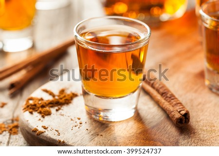 Cinnamon Whiskey Bourbon in a Shot Glass Ready to Drink - stock photo