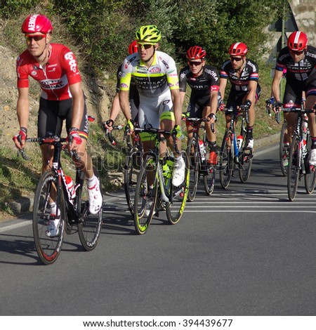 Cipressa, Italy - March 19, 2016: Group of cyclists ride uphill during international cycling race Milan ??Sanremo. With a distance of 298 km it is the longest professional one-day race in modern cycling - stock photo