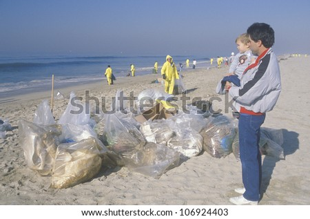 CIRCA 1990 - A man holding his child observing efforts to clean up an oil spill in Huntington Beach, California - stock photo