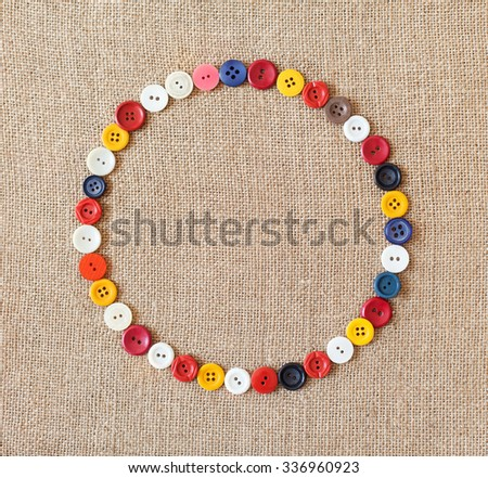 Circle from buttons on fabric texture background with copy space - stock photo
