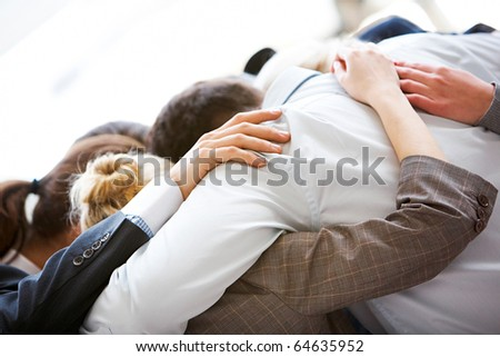Circle of business people embracing each other with their heads bowed while concentrating - stock photo