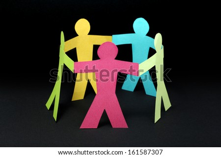 Circle of colorful paper people on black background - stock photo