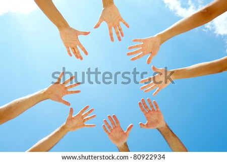 Circle of hands against blue sky - stock photo