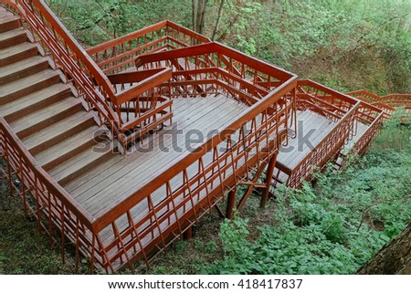 Circle red wooden stairs in a mountain forest. Long stairs labyrinth in a forest. Red wooden stairs path. Many stairs. Long descent down the stairs. Climbing a lot of stairs in deep forest. Red stairs - stock photo