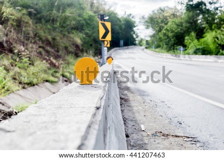Circle shape yellow road reflector plate which mount on bridge barrier - stock photo