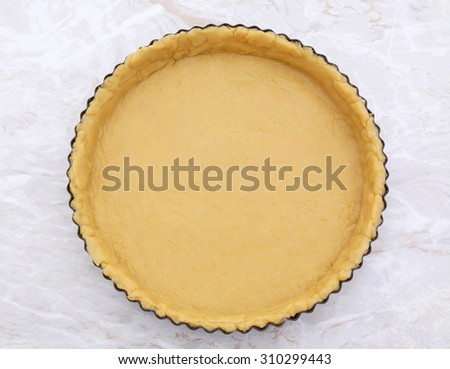 Circular metal flan tin lined with shortcrust pastry on a kitchen work surface - stock photo