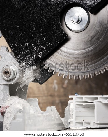 Circular saw blade cutting window fiber glass extruded profile - stock photo