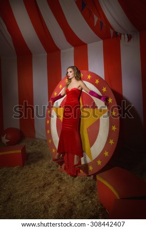 Circus actress in a red dress stands on circular disc with star  - stock photo