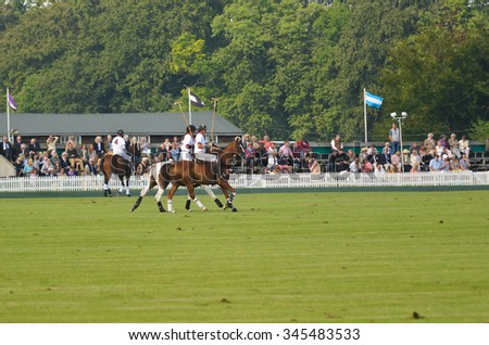 CIRENCESTER, UK - AUGUST 25, 2013: Polo players on horses in front of spectators in the stadium while playing at the Cirencester Park Polo Club in Cirencester, UK on August 25, 2013. - stock photo