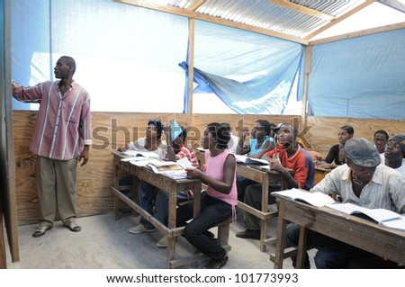CITE SOLEIL- AUGUST 25:  Students listening to their teacher in a local community school in Cite Soleil- one of the poorest area in the Western Hemisphere on August 25 2010 in Cite Soleil, Haiti. - stock photo