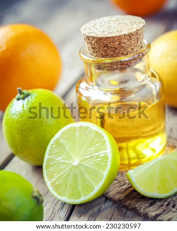 citrus essential oil and slice of orange, lemon and lime fruits on old wooden table - stock photo