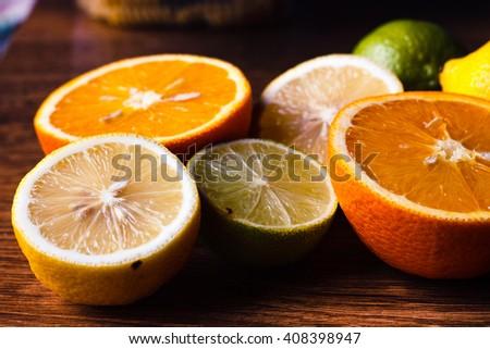 Citrus fruit cut in half - oranges, lemons, tangerines, grapefruit on a wooden background - stock photo