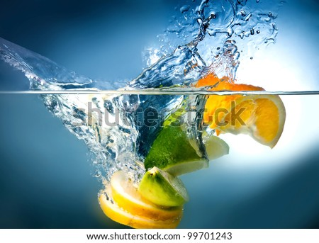 citrus fruits fall into the water - stock photo