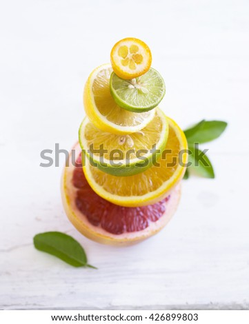 Citrus fruits family cut in half stocked on white wooden background. Stylized food image. - stock photo