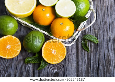Citrus fruits in basket. Oranges, limes and lemons - stock photo