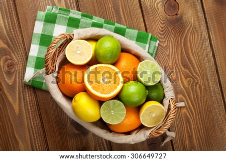 Citrus fruits in basket. Oranges, limes and lemons. Over wooden table background - stock photo