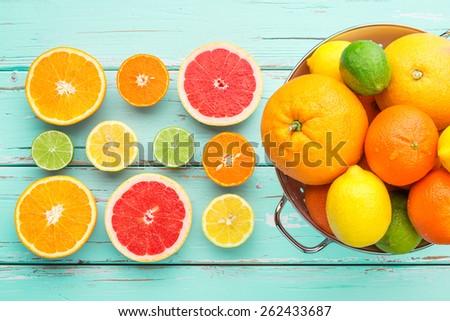 Citrus fruits in retro colander. - stock photo