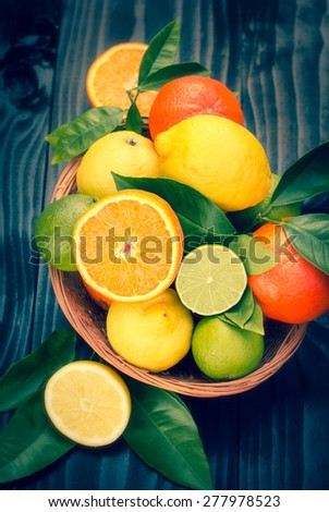 Citrus fruits in the basket on the rustic table - stock photo