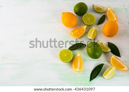 Citrus fruits mix on light green background. Healthy eating concept with lime and lemon. Fresh vegetarian food. Fresh mixed fruit. Fruit background.  - stock photo