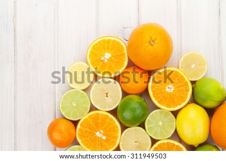 Citrus fruits. Oranges, limes and lemons. Over wooden table background with copy space - stock photo