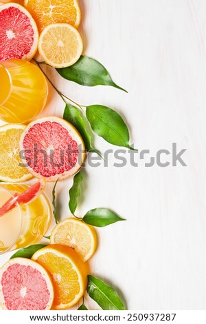 Citrus fruits  with green leaves and glass with juice on white wooden table , frame with place for text - stock photo