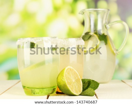 Citrus lemonade in pitcher and glasses on wooden table on natural background - stock photo