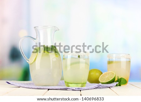 Citrus lemonade in pitcher and glasses on wooden table on room background - stock photo