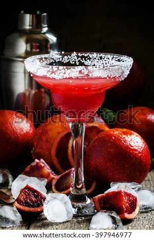 Citrus margarita cocktail with tequila, ice and blood orange juice, a glass garnished with salt, black background, selective focus - stock photo