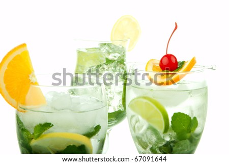 Citrus Mojito cocktails with light rum, vodka, gin, lime, spring of mint, simple soda, orange, maraschino cherry and syrup in cocktail glasses isolated on a white background - stock photo