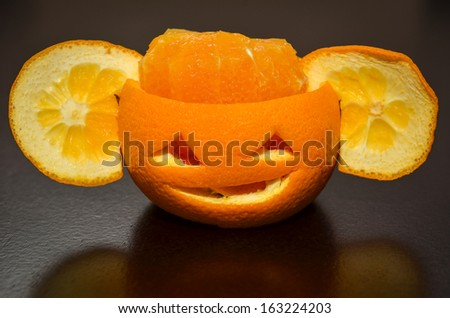 Citrus Orange Fruit Carved As A Pumpkin Face With Ears - stock photo