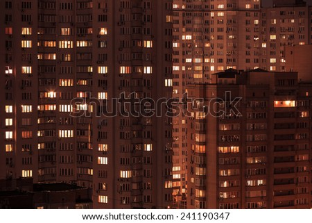 City at night. Pattern of night city windows of modern residential building - stock photo