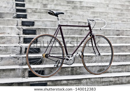 City bicycle fixed gear and concrete stairs. Vintage retro road bike over gray urban background, vintage retro style bike over grunge city urban environment, ecological transportation concept - stock photo