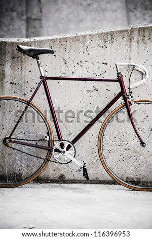 City bicycle fixed gear and concrete wall, commuting to work in city, vintage retro style bike over grunge city urban environment, ecological transportation concept - stock photo
