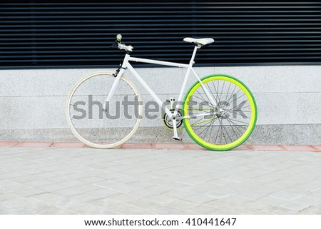 City bicycle fixed gear on wall. Cycling or commuting in city urban environment, ecological transportation concept. - stock photo
