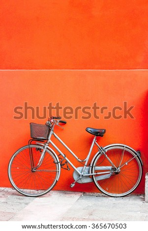 City bicycle parked against orange wall. - stock photo