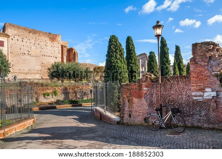 City bicycle stand leaning on old brick wall and lamppost on narrow street in Rome, Italy. - stock photo