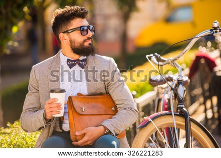 City bike. A young man with a beard, walk the city with bike - stock photo