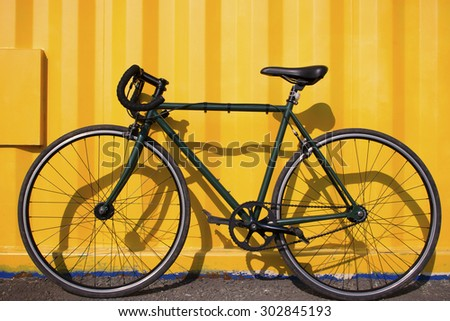 city bike fixed gear on a yellow background selective focus - stock photo