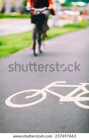 City bike sign on asphalt bikepath, colorful vintage light on street, commute on classic bicycle in urban environment, colorful background - stock photo