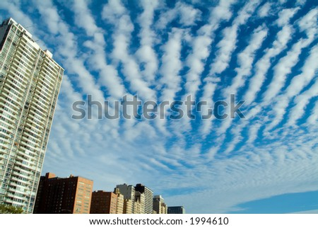 City buildings skyline with dramatic clouds - stock photo