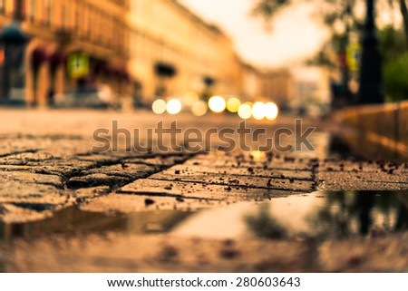 City central square paved with stone after a rain, headlights from cars in the distance. View from the pavement level next to the roadside puddle, image in the yellow toning - stock photo
