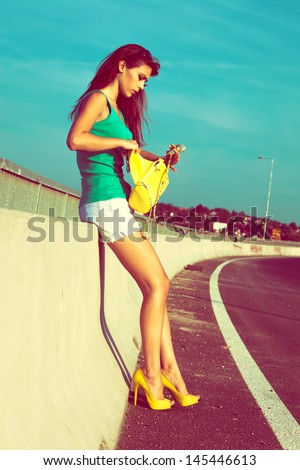 city girl in green top tank shorts and high heel shoes on the street day shot - stock photo