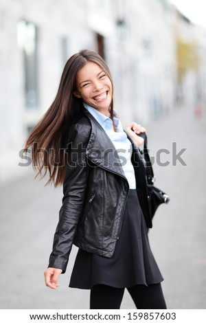 City girl - modern urban woman smiling happy from the heart. Female fashion wearing black leather jacket walking outside in street. Lovely beautiful multi-ethnic Caucasian Asian girl in her 20s. - stock photo