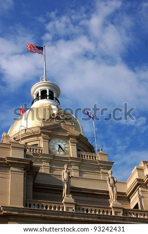 City Hall of Savannah, GA was built in 1901 of granite blocks. The two statues represent art and commerce, and the dome, originally clad in copper, was gilded in 1987. - stock photo