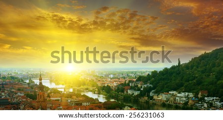 city in a mountain valley and sunrise - stock photo