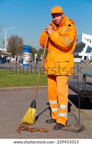 City landscaper janitor with broom tool during street sweeping - stock photo