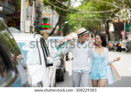 City life: cheerful young couple with shopping bags walking in the street - stock photo